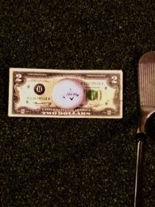 Most generally the dollar bill is used for bunker shots to be able to hit behind and under the golf ball to get the ball up and out of the bunker. Here in this instance the 2-Dollar bill is used to fine tune your impact with the golf ball. The 2-Dollar bill can actually be used to develop a nice rhythm and great tempo into the impact area of with the ball.