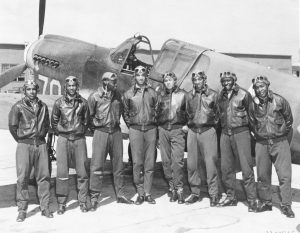 Tuskegee Airmen (Red Tails) posing in front of a P-40 Warhawk.